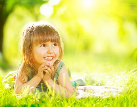 Photo pour Portrait of a smiling little girl lying on green grass - image libre de droit