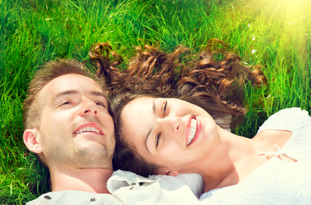 Happy smiling couple relaxing on green grass