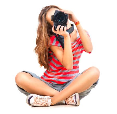 Photo pour Beauty teenage girl photographer sitting over white background - image libre de droit