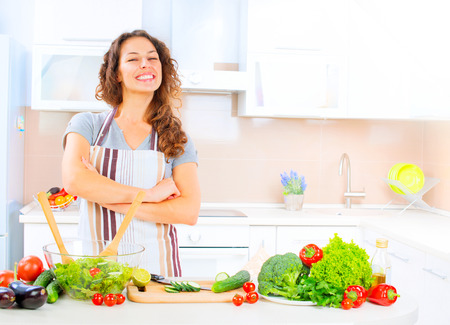 Photo for Happy young woman cooking in the kitchen at home - Royalty Free Image