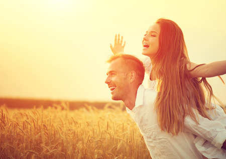 Photo pour Happy couple having fun outdoors on wheat field over sunset - image libre de droit