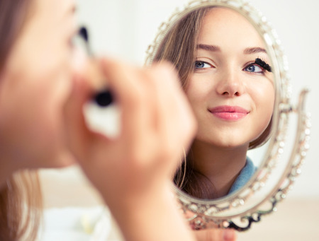 Foto de Beauty model teenage girl looking in the mirror and applying mascara - Imagen libre de derechos