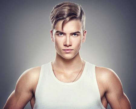 Foto de Handsome athletic young man isolated on grey background - Imagen libre de derechos