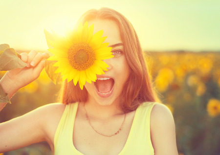 Photo pour Beauty joyful teenage girl with sunflower - image libre de droit