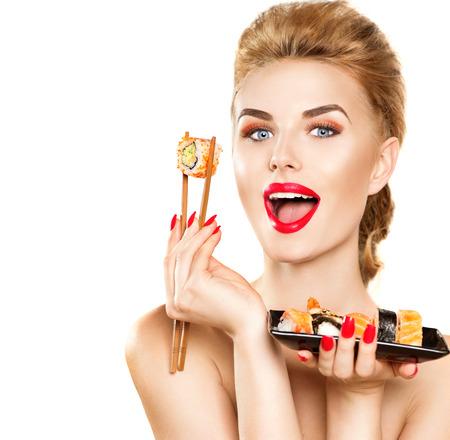 Beauty fashion model girl eating sushi rolls