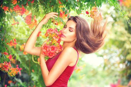Beauty model girl enjoying nature in garden with beautiful tropical flowers