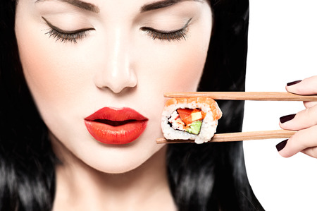Foto per Fashion art portrait of beauty model girl eating sushi roll - Immagine Royalty Free