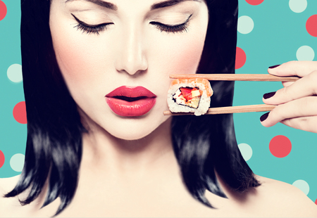 Photo for Beautiful woman holding chopsticks with sushi roll - Royalty Free Image