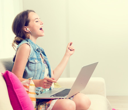 Photo for Beautiful teenage girl sitting on sofa at home, using laptop computer, laughing and having fun. Happy Teenage girl enjoying the music with headphones and dancing. Emotions. Happiness. Good mood - Royalty Free Image