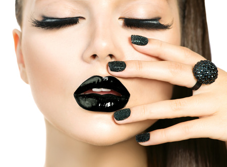 Photo pour Beautiful Fashion Model woman with Long lashes and Black make up isolated on white. Fashion Trendy Caviar Black Manicure. Nail Art. Dark Lipstick and Nail Polish. Vogue style - image libre de droit