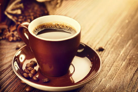 Photo pour Cup of aromatic coffee over wooden table. Coffee beans - image libre de droit