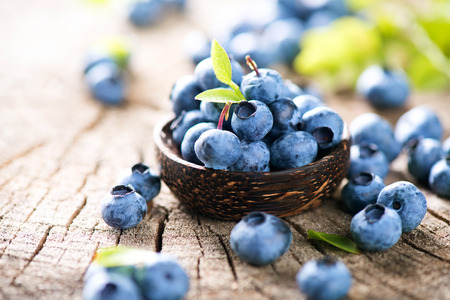 Foto de Juicy and fresh blueberries with green leaves in wooden bowl - Imagen libre de derechos