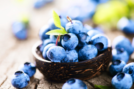 Photo for Blueberries in wooden bowl over rustic wooden table closeup - Royalty Free Image