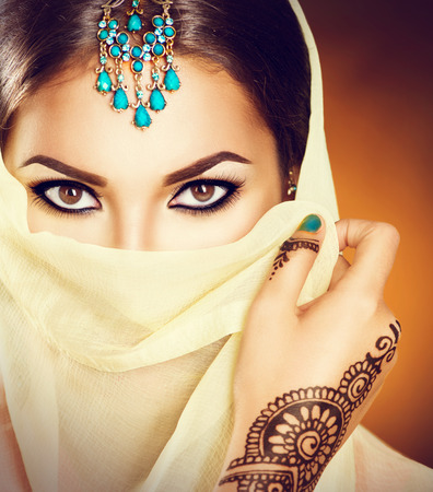 Photo for Beautiful indian woman with traditional turquoise jewels hiding her face - Royalty Free Image