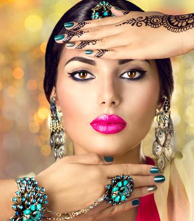 Photo pour Beautiful indian woman portrait. Hindu girl with oriental accessories - earrings, bracelets and rings - image libre de droit