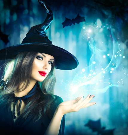 Photo for Halloween Witch holding magical light in her hand - Royalty Free Image