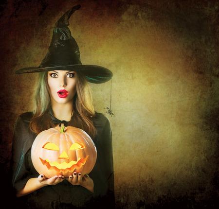 Foto de Halloween Witch holding carved Jack lantern pumpkin - Imagen libre de derechos
