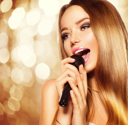Photo for Singing teenage girl with microphone over golden glowing background. Karaoke party - Royalty Free Image