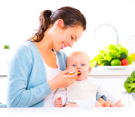 Foto de Mother feeding her baby girl with a spoon. Baby food - Imagen libre de derechos