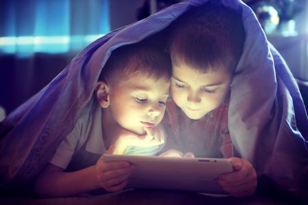 Foto de Two kids using tablet pc under blanket at night - Imagen libre de derechos