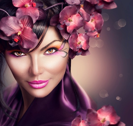 Beautiful woman with orchid flower hairstyle and creative makeup