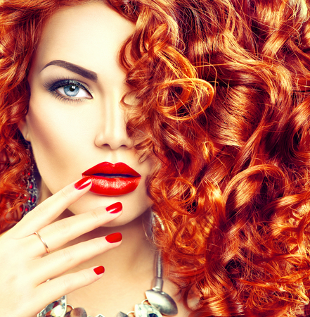 Foto de Beauty young woman with curly red hair, perfect makeup and manicure - Imagen libre de derechos