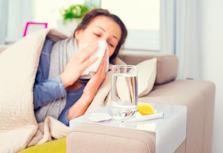 Foto de Flu. Sick woman sneezing into tissue - Imagen libre de derechos