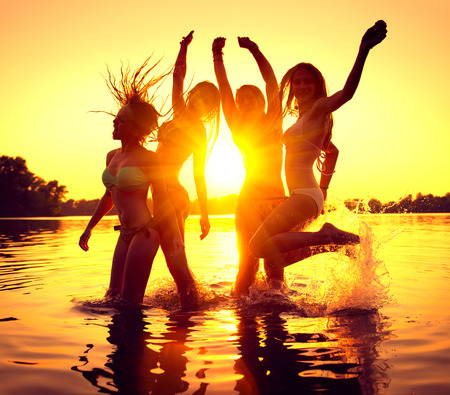 Photo for Beach party. Group of happy girls dancing in water on beautiful summer sunset - Royalty Free Image