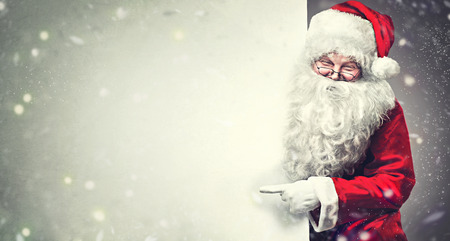Foto de Smiling Santa Claus pointing on blank advertisement banner background with copy space - Imagen libre de derechos
