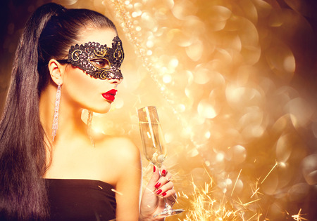 Foto de Sexy model woman with glass of champagne wearing venetian masquerade mask at party - Imagen libre de derechos
