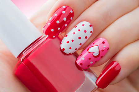 Photo pour Valentines Day holiday style bright manicure with painted hearts and polka dots - image libre de droit