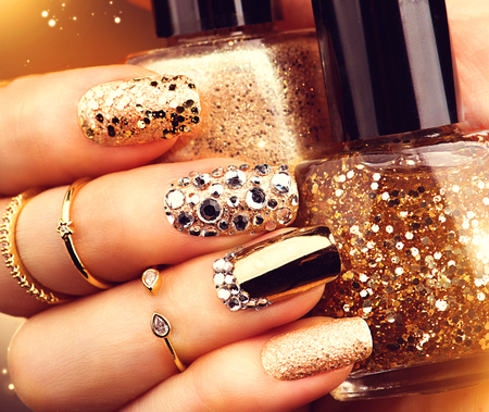 Photo for Golden holiday style bright manicure with gems and sparkles. Trendy accessories - Royalty Free Image