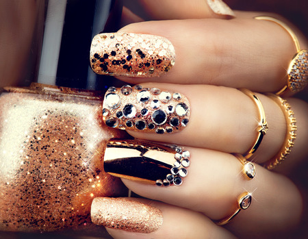 Photo pour Golden holiday style bright manicure with gems and sparkles. Trendy accessories - image libre de droit