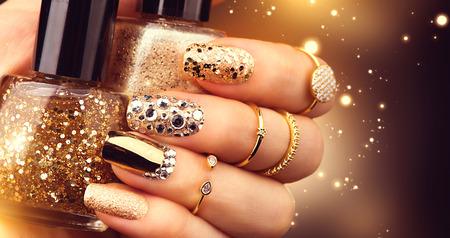 Photo pour Golden manicure with gems and sparkles. Bottle of nailpolish, trendy accessories - image libre de droit