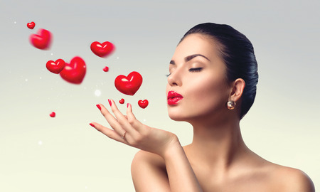 Photo pour Beauty woman with perfect make up blowing valentine hearts - image libre de droit