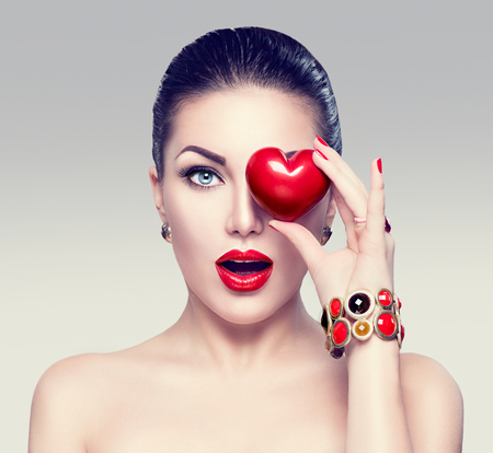 Foto de Fashion woman with red heart. Valentine's day art portrait - Imagen libre de derechos