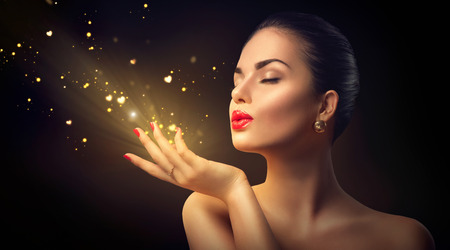Photo for Beauty young woman blowing magic dust with golden hearts - Royalty Free Image