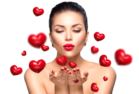Foto de Beauty woman with perfect makeup blowing Valentine hearts - Imagen libre de derechos