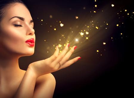 Photo pour Beauty young woman blowing magic dust with golden hearts - image libre de droit