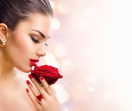 Foto de Fashion model girl face portrait with red rose in her hand - Imagen libre de derechos