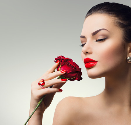 Photo pour Fashion model girl portrait with red rose in her hand - image libre de droit
