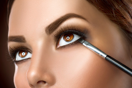 Photo pour Woman applying makeup closeup. Eyeliner - image libre de droit