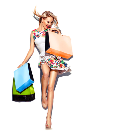 Foto de Beauty woman with shopping bags in short white dress. Shopping - Imagen libre de derechos