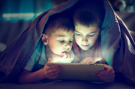 Photo pour Two kids using tablet pc under blanket at night - image libre de droit