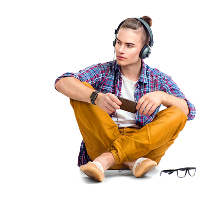 Photo for Young fashion man sitting on the floor and enjoying music - Royalty Free Image