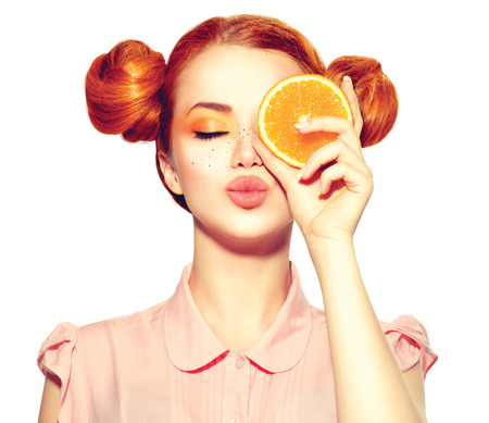 Photo for Beautiful joyful teen girl with freckles holding juicy orange slice - Royalty Free Image