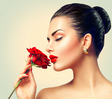 Foto de Fashion brunette model girl face portrait with red rose in her hand - Imagen libre de derechos