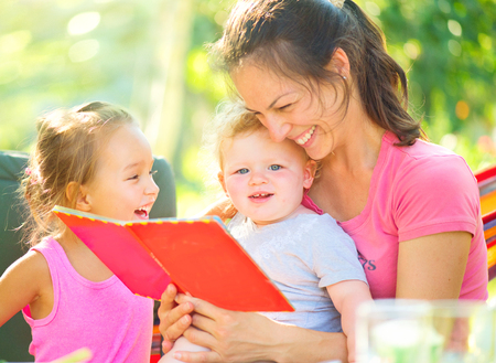Photo pour Happy mother reading a book to her children in sunny park - image libre de droit