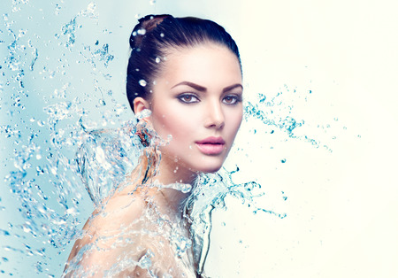 Photo for Beauty spa woman under splash of water over blue background - Royalty Free Image