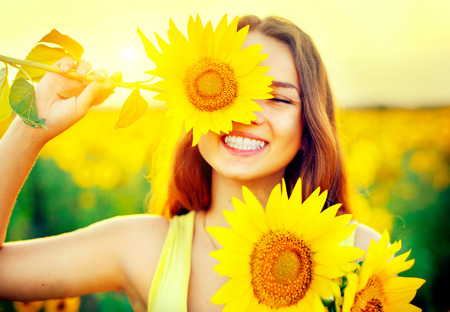 Photo pour Beauty joyful teenage girl with sunflower enjoying nature - image libre de droit